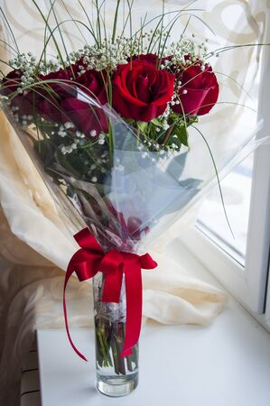 The color of vinous red color is standing in the vase on the table. Green leaves and thorns. Wide red bow. Calm light background