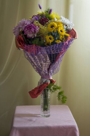 A bouquet of flowers of different shades on a background of green curtains. Roses, carnations, chrysanthemums and asters 免版税图像 - 139602741