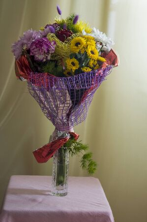 A bouquet of flowers of different shades on a background of green curtains. Roses, carnations, chrysanthemums and asters 免版税图像 - 139602736