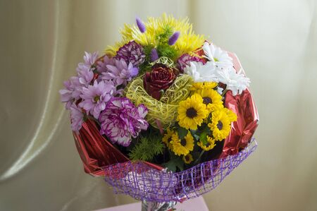 A bouquet of flowers of different shades on a background of green curtains. Roses, carnations, chrysanthemums and asters Stock Photo