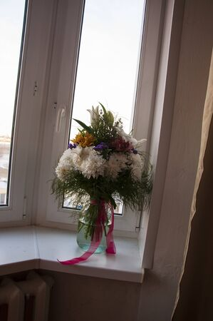White lilyes, yellow and pink orchids, branch of lilac, chrysanthemums in the spring tender bouquet on the background with window