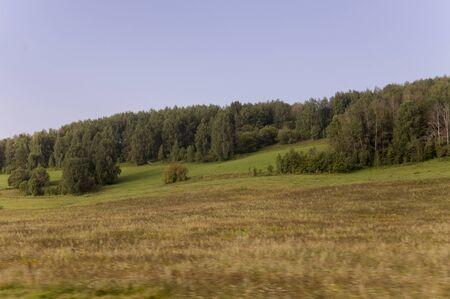 Soft lands?ape with green meadows and mountains far away. Light blue sky. Summer fields 版權商用圖片