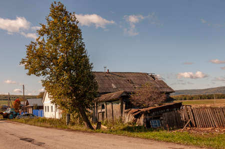 Autumn sky over village with small wood colored local house and low fence in the mountains and fields. Traveling on the suburb roads. People living