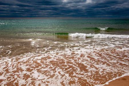 Black Sea. Water with waves. Dark cloudy weather. Deep bright blue water. Before storm. Sand coast 版權商用圖片
