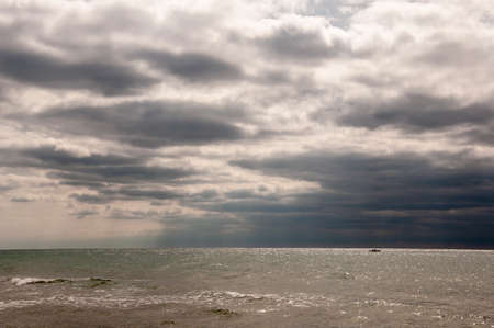 Black Sea. Water with waves. Mainly cloudy weather and sun rays in the evening. Deep bright blue water. Before rain. Little boat far away