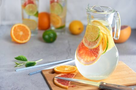 Health care, fitness, healthy nutrition diet concept. Fresh cool homemade citrus infused detox water with grapefruit, orange, lemon and lime and ice in a jug and glasses for spring summer days.