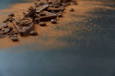 Dark chocolate stack, chips and cocoa powder with coffee beans on a dark background. Confectionery and food concept. Top view, copy space, selective focus. Standard-Bild