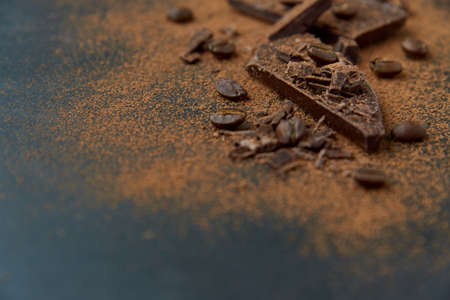 Dark chocolate stack, chips and cocoa powder with coffee beans on a dark background. Confectionery and food concept. Top view, copy space, selective focus.. Standard-Bild