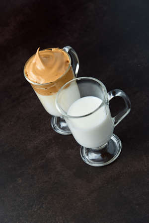 Glasses of trendy fluffy creamy dalgona or whipped instant coffee with milk on the dark background. New popular food and drink trend concept. Copy space.