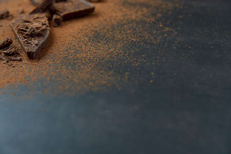Dark chocolate stack, chips and cocoa powder on a dark background. Confectionery and food concept. Top view, copy space, selective focus..