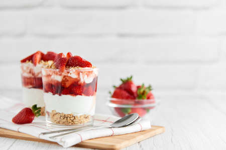 Homemade layered dessert with fresh strawberries, cream cheese or yogurt, granola and strawberry jam in glasses on white wood background. Healthy organic breakfast or snack concept. Selective focus.