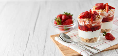 Homemade layered dessert with fresh strawberries, cream cheese or yogurt, granola and strawberry jam in glasses on white wood background. Healthy organic breakfast or snack concept. Selective focus. Banque d'images