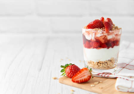 Homemade layered dessert with fresh strawberries, cream cheese or yogurt, granola and strawberry jam in glass on white wood background. Healthy organic breakfast or snack concept. Selective focus.