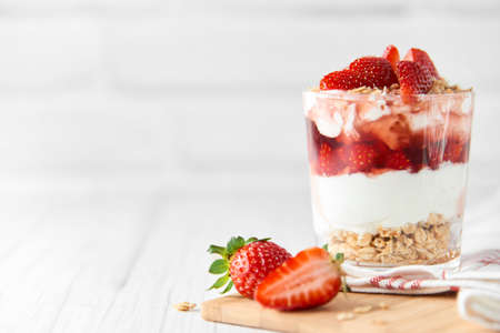 Homemade layered dessert with fresh strawberries, cream cheese or yogurt, granola and strawberry jam in glass on white wood background. Healthy organic breakfast or snack concept. Selective focus. Banque d'images