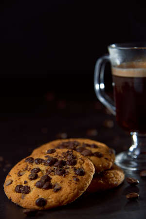 Close up of a glass cup of coffee, chocolate chip cookies and roasted coffee beans on dark background. Concept of ready to eat food, tasty snack. Selective focus, copy space.