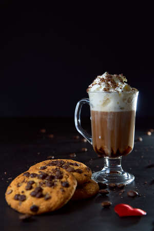 Close up of a glass cup of coffee with whipped cream and chocolate on it, chocolate chip cookies and roasted coffee beans on dark background. Concept of ready to eat food, tasty snack. Selective focus