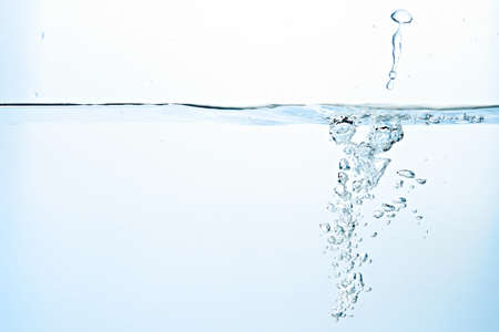 Close up of clean blue water and splash with bubbles of air isolated on white background. Diet, health and nature concept. Copy space ..