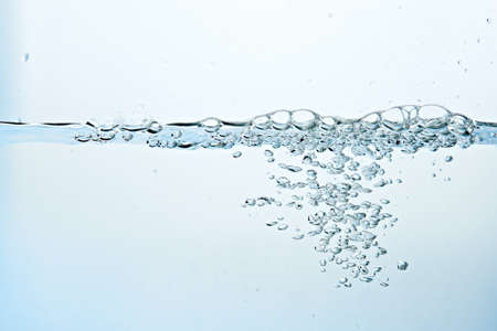 Close up of clean blue water and splash with bubbles of air isolated on white background. Diet, health and nature concept. Copy space .. Archivio Fotografico