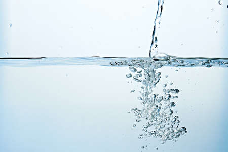 Close up of clean blue water and splash with bubbles of air isolated on white background. Diet, health and nature concept. Copy space .. Фото со стока