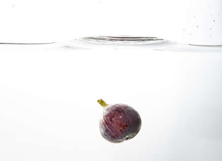 Fresh figs falling deeply into clear water isolated on a white background. Healthy food diet freshness concept. Copy space ..