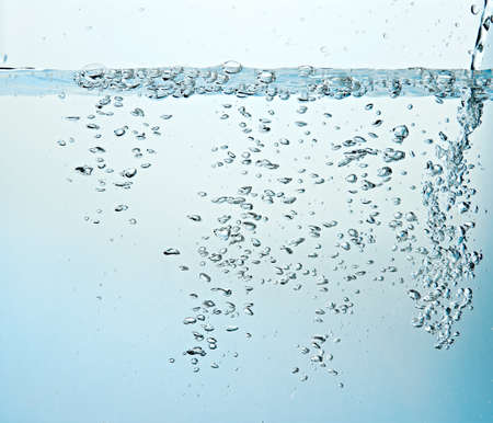 Close up of clean blue water and splash with bubbles of air isolated on white background. Diet, health and nature concept. Copy space .. Banco de Imagens
