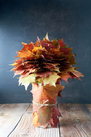 Bouquet or bunch made from colorful autumn leaves isolated on wooden background. Autumn, fall, thanksgiving day, nature concept. Flat lay, top view, copy space .. Archivio Fotografico