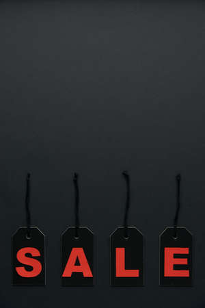 Word sale written on black cardboard paper labels or price tags with cord isolated on dark background. Black Friday, Shopping, sale and marketing concept. Top view, flat lay, copy space.