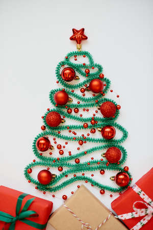 Christmas tree made from winter decorations on white background with empty copy space for text. Holiday and celebration creative concept. New year and christmas postcard or invitation. Top view