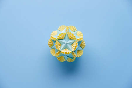Multicolor handmade modular origami ball or Kusudama Isolated on blue background. Visual art, geometry, art of paper folding, paper crafts. Top view, close up, selective focus, copy space.