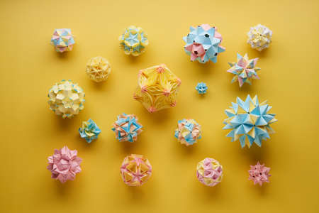 Set of multicolor handmade modular origami balls or Kusudama Isolated on yellow background. Visual art, geometry, art of paper folding, paper crafts. Top view, close up, selective focus, copy space.