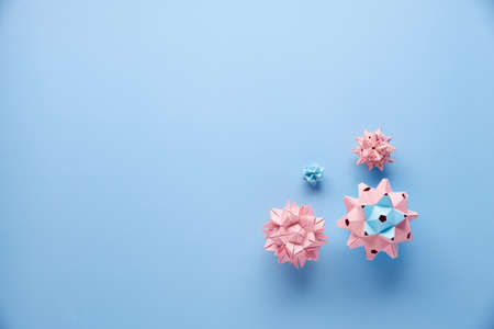 Set of multicolor handmade modular origami balls or Kusudama Isolated on blue background. Visual art, geometry, art of paper folding, paper crafts. Top view, close up, selective focus, copy space.