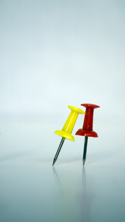 two colorful pushpins on white blue  background. Yellowpushpins bends to red
