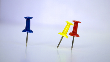 three colorful pushpins on white background.Yellow pushpins bends to red