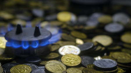 Ukrainian crisis. The concept of high prices for natural gas. Blue flames of natural gas burning from a gas stove with ukrainian coins