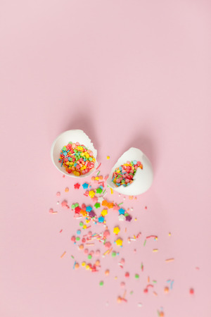 White Easter eggs on a light pink background, broken egg with colored decorations, minimalistic design, vertical shot