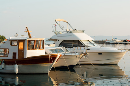 Yachts are moored in the marina, beautiful sunlight illuminates them early in the morning, calm and serenity