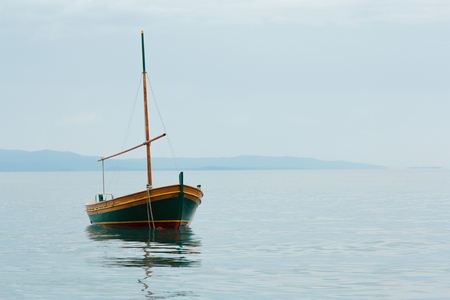 old rusty fishing boat stands empty on the water, blue sky and blue water, summer