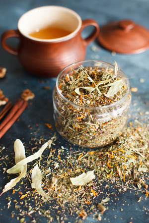 echinacea: Clay pot with honey, cinnamon sticks, nuts and a herb collection scattered on a blue table, a glass jar with tea, lime, mint, lemon balm, chamomile. Daylight, vertical image.