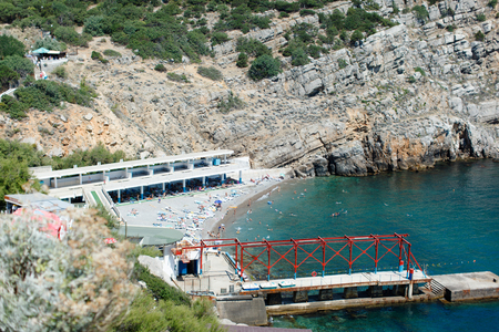 Sea bay, beach, pier. Holidaymakers sunbathe, bathe in the sea. Summer, vacation, Yalta, Crimea.