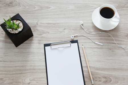 constitute: Workplace. On the wooden table is a folder with a clip, a white sheet with space for text, pot with plant, a pan and white cup of coffee.