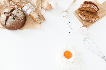 Cooking of homemade bread, black round bread and baguette lie on parchment paper on a white background with flour, sliced bread, paper, salt and eggs. Space for text, daylight. Stock Photo