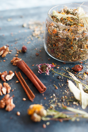 lemon balm: Cinnamon sticks, nuts and a herb collection scattered on a blue table, a glass jar with tea, lime, mint, lemon balm, chamomile. Daylight, vertical image. Stock Photo