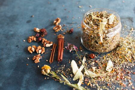 field mint: Cinnamon sticks, nuts and a herb collection scattered on a blue table, a glass jar with tea, lime, mint, lemon balm, chamomile. Daylight, vertical image. Stock Photo
