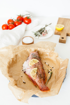 Cooking and marinating sea fish at home. Red perch with lemon, pepper and rosemary lies on parchment paper and is ready for baking. Stock Photo