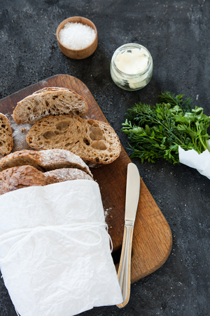 Sliced loaf of homemade bread, with salt, herbs and butter on a dark background. Daylight, space for your text