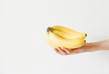 The girl is holding a bunch of bananas in her hand. Daylight, space for your text