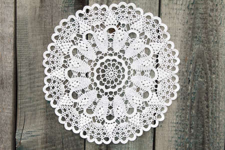 Beautiful crochet doily on old wooden background Stock Photo
