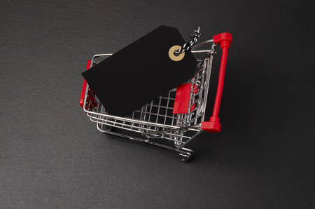 Shopping cart on the black background. Shopping card with a price tag. Shopping concept.