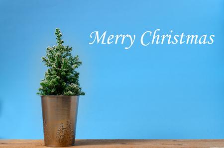 Mini Christmas tree on blue background. Minimalistic concept.