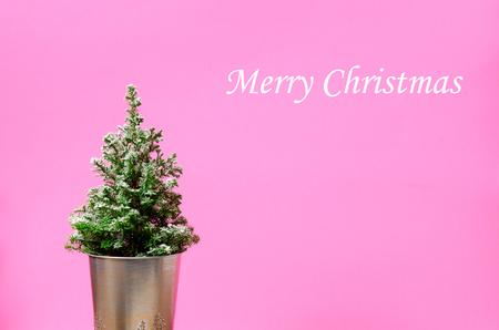 Mini Christmas tree on pink background. Minimalistic concept.
